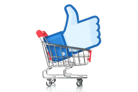 37181942 - kiev, ukraine - january 24, 2015: facebook thumbs up sign printed on paper and placed into shopping cart on white background. facebook is a well-known social networking service.